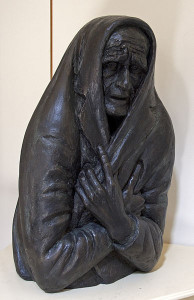 Sculpture of woman huddled in a jacket