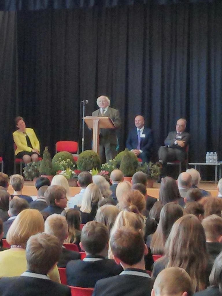 President Higgins standing at a lecturn speaking to the school audience.